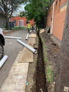 crew installing drainage and moisture barriers along exterior of brick property